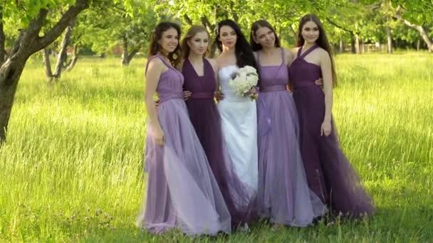 cb45e7e7f993 Συναισθηματική νύφη και παράνυμφων μιλά και να χαμογελά. Λατίνες σε μωβ  φορέματα θέτοντας σε εξωτερικούς χώρους– πλάνα αρχείου