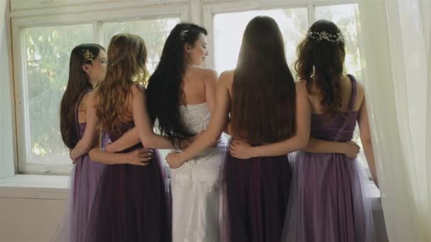 Nevěsta se objímá s družičky ve studiu. Krásné dívky v fialové šaty se smát na okno. Ženy představují během ranní nevěsta