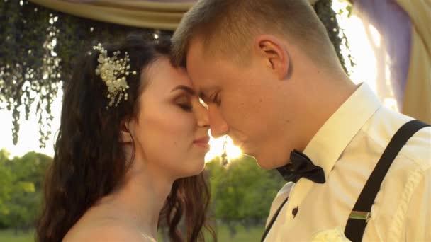 Detail šarmantní pár. Kavkazská novomanželé zavře oči radostí. Milující pár objímaly při západu slunce