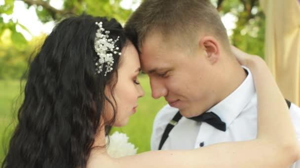 Detail je okouzlující mladý pár. Kavkazská novomanželé zavře oči radostí. Dívka s hřebenem ve vlasech drží její boyfriendloving pár objímaly při západu slunce