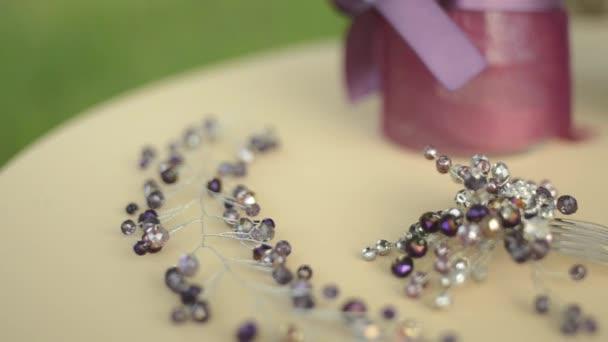 Svatební doplňky na stůl. Fialové květy, béžové tkaniny, brož nebo hřeben do vlasů pro nevěsty. Variabilní zaměření, detail
