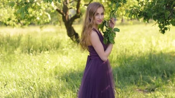 Portrét krásné dívky s světlý make-up. Kavkazské blond žena s kyticí pózuje a při pohledu na fotoaparát v lila nebo fialové šaty v zahradě