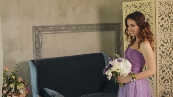 Portrét krásné dívky s profesionální make-up. Kavkazské bruneta žena s kyticí pózuje a při pohledu na fotoaparát v lila nebo fialové šaty v ateliéru