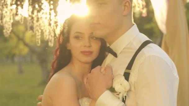 Elegantní svatební šťastný pár, nevěsta a ženich objímání v parku při západu slunce