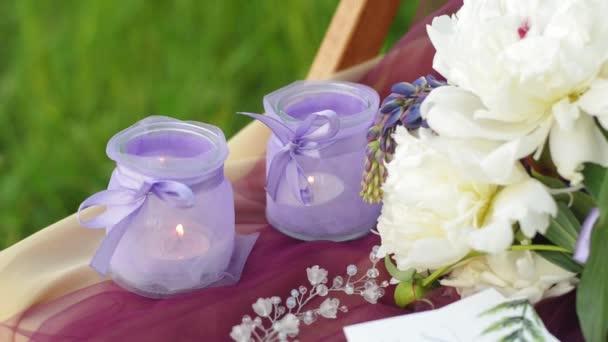 Hochzeitsdekoration in violetten Farben. Leuchter mit brennenden Kerzen. Hochzeitskranz und Strauß Lupinen und Peons.