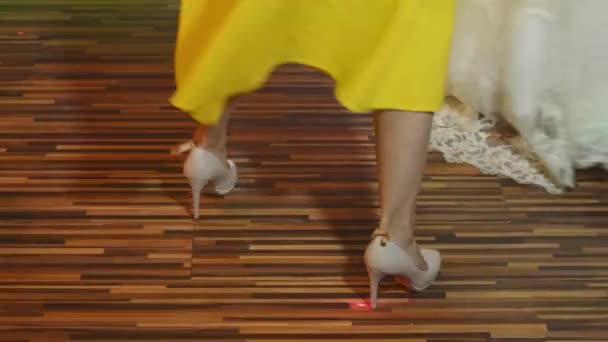 dbb3cf009 Две женщины танец в ночном клубе, показано в движении с только ногами  видны. Одна девочка в белом платье, второй в желтом платье и обувь–  стоковое видео