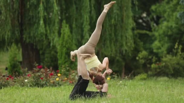 schönes Paar praktiziert Acroyoga. Yogalehrer üben in einem Stadtpark auf grünem Gras. Zwei erfolgreiche junge Leute führen Akro-Yoga-Übungen vor. Mann und Frau lernen Yoga bei Sonnenuntergang.