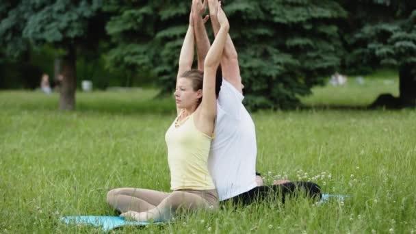 Egy férfi és egy nő, stretching gyakorlatok végrehajtása előtt. Fiatal oktatók jóga a Városligetben, a zöld fű. Sikeres fiatalok végre acro jóga gyakorlatok.