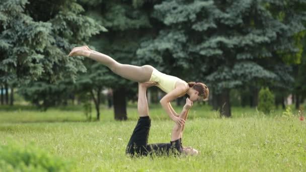 Gyönyörű pár acro jóga. Fiatal oktatók jóga a Városligetben, a zöld fű. Két sikeres fiatalok végre acro jóga gyakorlatok. Férfi és egy nő meg tanulni jóga naplementekor.