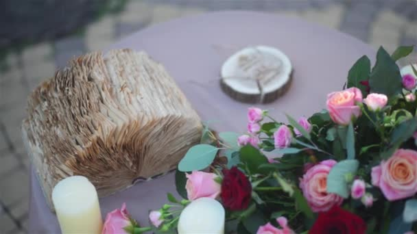 Beautiful wedding decorated table setted for two on nature in the garden. Wedding decoration in violet and red colors. Flowers, candles and decorative old book. Slow pan.