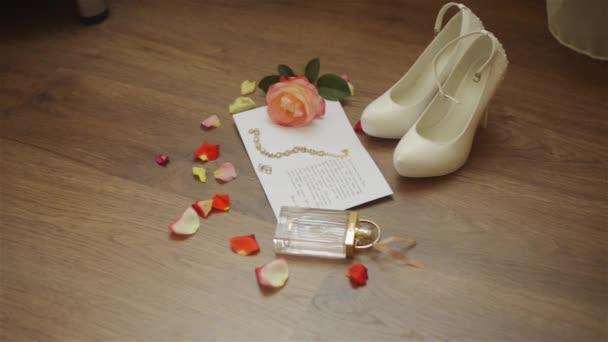 Složení svatební. Ráno nevěsty. Detail svatební bílé boty na vysokých podpatcích. Kroužky, okvětních lístků růže a svatební pozvánky na podlaze.