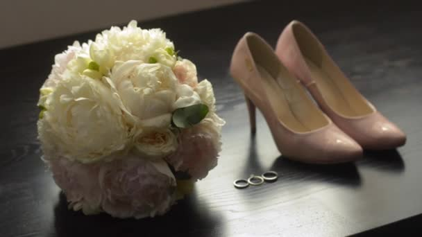 Brides morning details. Beautiful bridal bouquet, wedding rings. Wedding composition on a black wooden surface. Morning of the bride. Close up of wedding shoes on high heels.