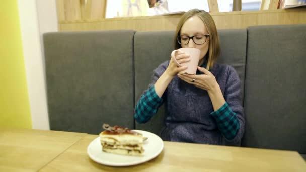 Zasněný mladá dívka v brýlích pití horké skandinávské čaj s borůvkami a mátou z růžového poháru a odpočinku v kavárně, s úsměvem a při pohledu na fotoaparát. Dort, zvané švédské Espresso na talíři