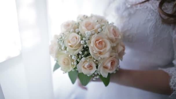 Sposa in abito da sposa che tiene bella bianco bouquet fiori