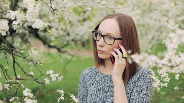 Sad girl in glasses speaking on cellphone in the blooming garden.