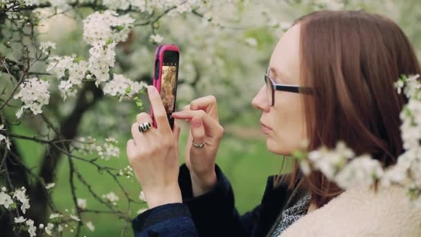 Casual woman taking photos of blossom spring tree flowers on a smartphone.