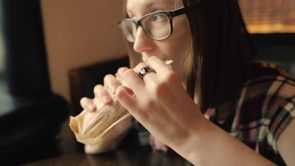 Closeup hlad žena v brýlích je jíst chutné kuřecí shawarma