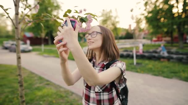 Young attractive woman in glasses taking selfie with sakura flowers.