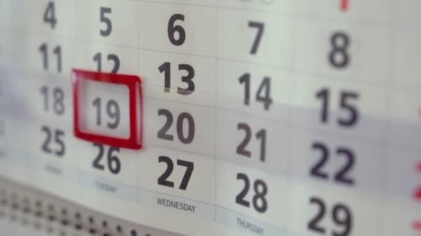 Obchodník prstem tlačí červenou značku na stránce kalendáře. Tlačí na papírový kalendář. Značka kalendáře tlačítek na papíře může být poslední dny. Koncept kanceláře, konference, kalendář a samolepka 4k