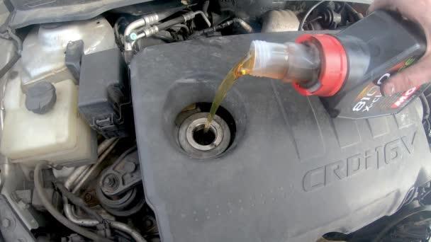 Pruszcz Gdanski, Polsko - 28. dubna 2020: Lití motorového oleje Motul 5W30 do motoru v autě.