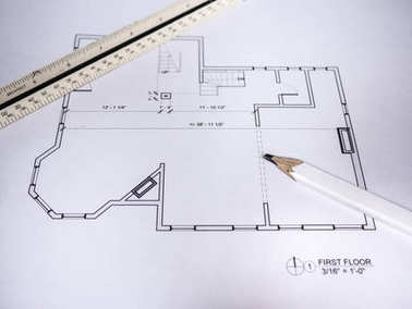 Photograph of generic architectural residential floor plan drawings printed on white paper set on top of a wood desk in a architect studio with scale ruler and carpenters pencil.