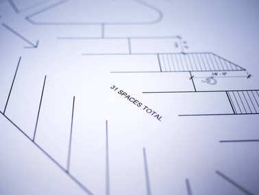 Photograph of generic architectural site plan drawings printed on white paper set on top of a wood desk in a architect studio.