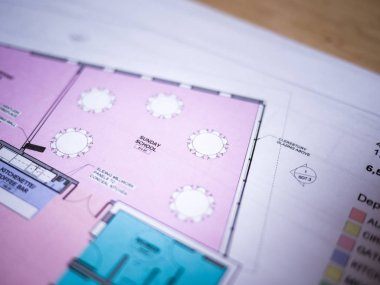 Photograph of generic colored architectural floor plan drawing printed on white paper set on top of a wood desk in a architect studio.