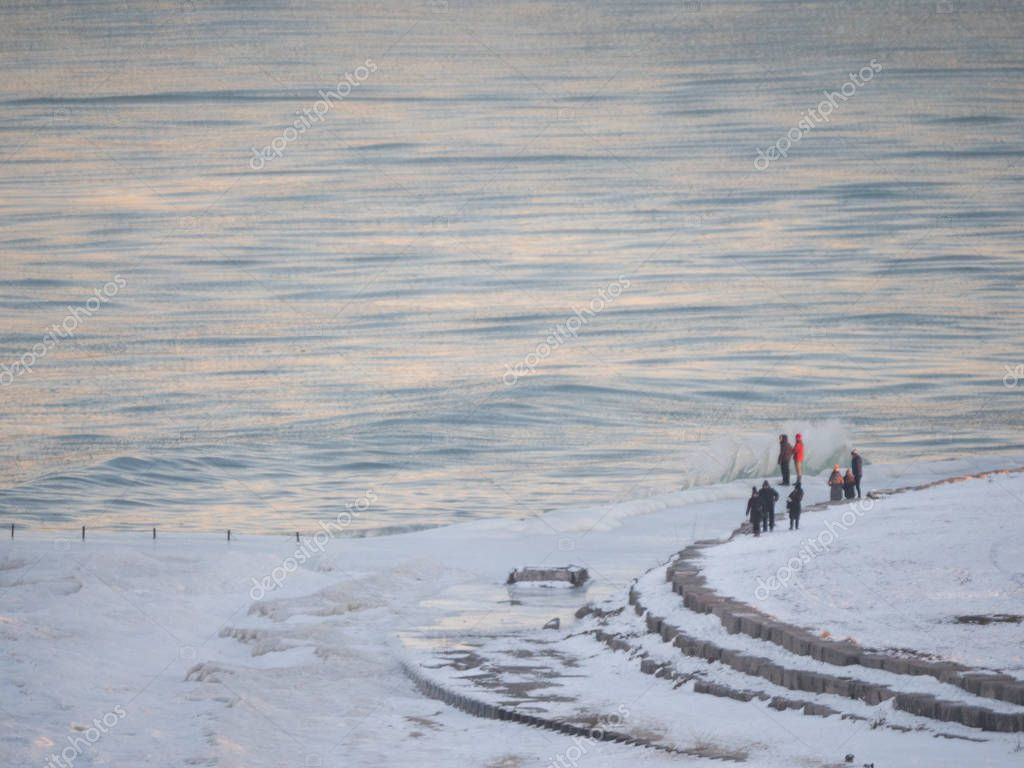 Chicago, IL - January 9th, 2018: People emerge from their homes to hang out along Lake Michigan at Foster Beach in Chicago after the bitter cold weather subsides.