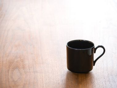 Close up background photograph of a single empty black porcelain or ceramic tea or coffee cup or mug isolated on a dark wood grain table and half heart shaped curved handles.