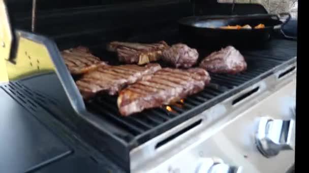 Detailní záběr rýžování klip z několika úst zalévání červené maso hovězí steaky včetně filet mignon, ribeye, a t-bone kusy značkami char na plynový gril s žluté plameny pod kovové rošty