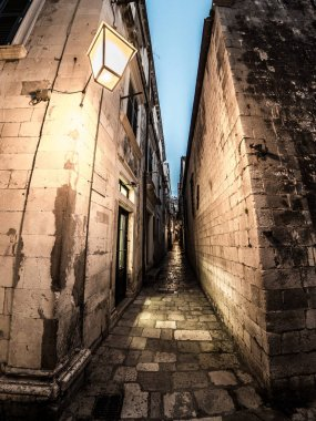 Beautiful night street photograph looking down a narrow stone paved pedestrian alley in the historic town of Dubrovnik in Croatia between buildings.