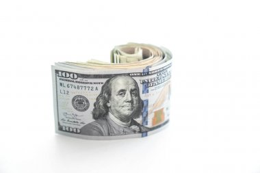 A rolled up wad of money with a Benjamin or United States hundred dollar bill on the top sits on edge and starts to unravel or unroll and is isolated on a white background with copy space.