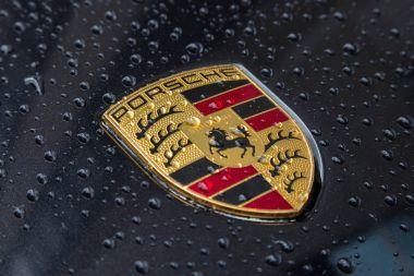 Porsche Logo Close Up on a black car with rain drops.