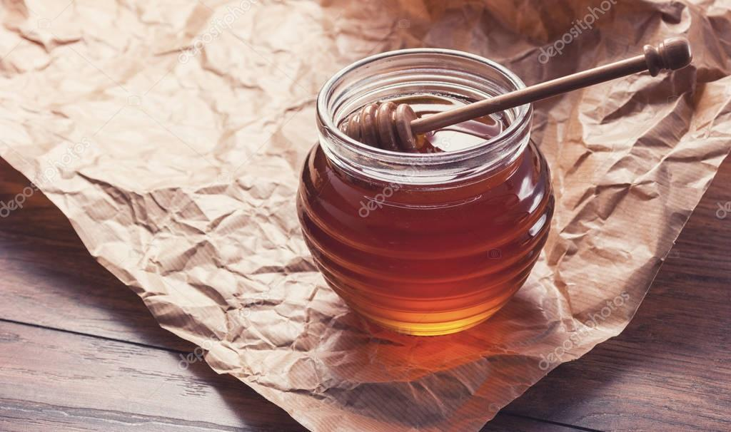 Honey in a pot or jar on paper with Honey dipper