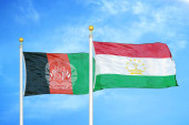 Afghanistan and Tajikistan  two flags on flagpoles and blue cloudy sky background