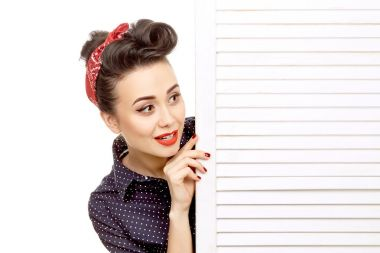 Looking out for news. Portrait of a gorgeous pin up woman with a retro hairstyle and red lips makeup peeking from behind the door copyspace isolated on white stock vector