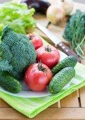 Čerstvá syrová zelenina a chléb s nožem na pozadí