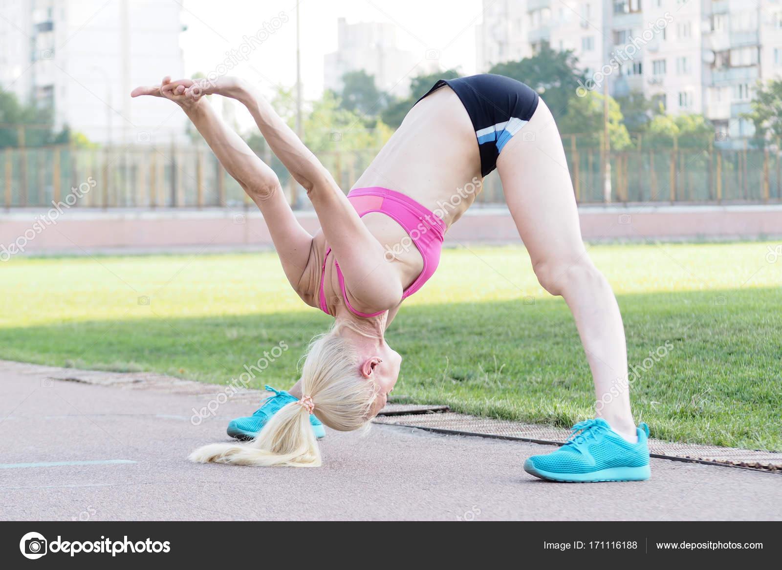 969c0f835cf2f7 Atrakcyjna kobieta czy rozciąganie z szerokim położeniu jej nogi i tilt,  jej ciało do przodu– obraz stockowy