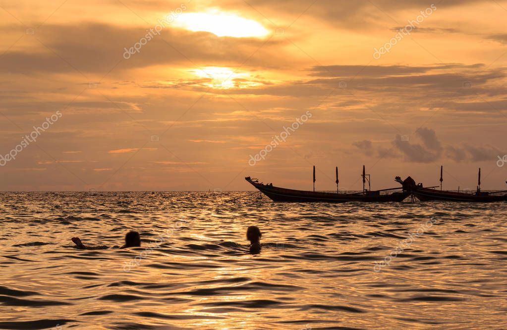 Silhouette of romantic lover swimming in ocean at sunset time, koh tao island, Suratthani, Thailan