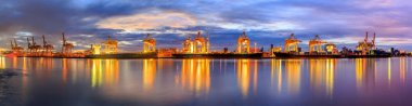Panorama image working crane loading bridge in shipyard at dusk for Logistic Import Export background