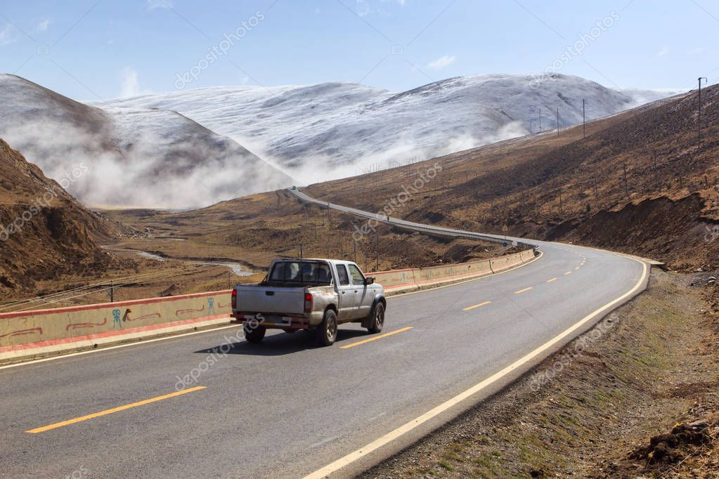 Pickup truck on the road, Beautiful winter road in Tibet under snow mountain Sichuan China