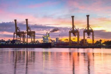Logistic Working crane loading bridge in shipyard at sunrise time for Logistic Import Export background
