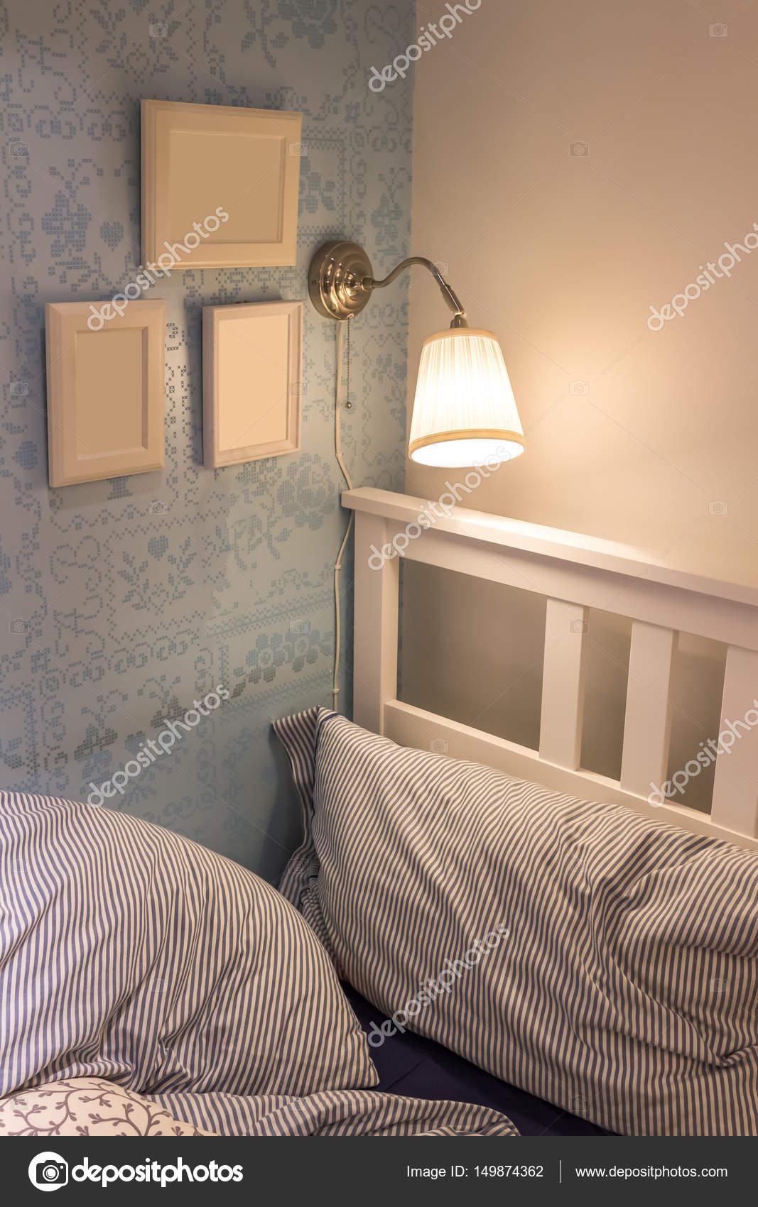 muur lamp boven bed gezellige slaapkamer stockfoto