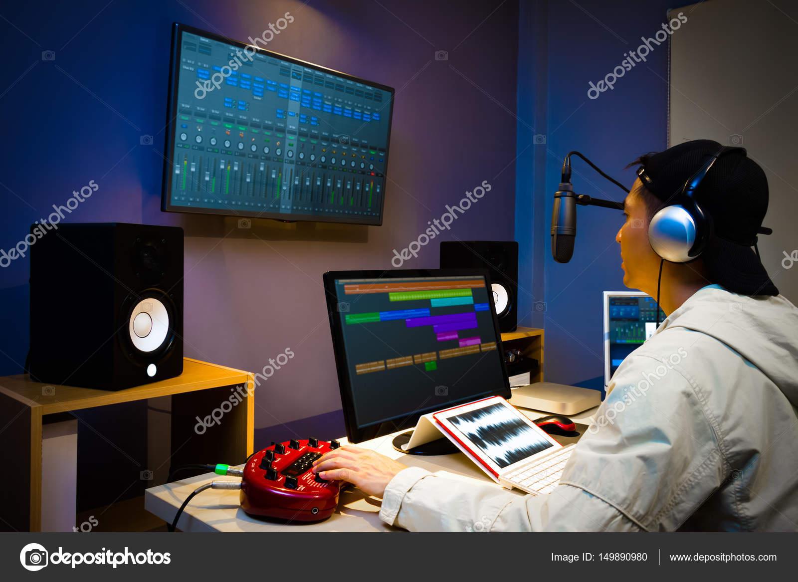 Asian male DJ working in digital broadcasting studio, online