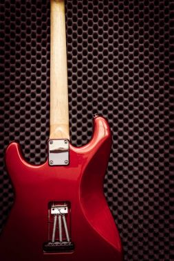 Back of red electric guitar on black acoustic board in recording studio for music background