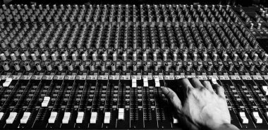 right hand of sound engineer working on recording studio mixer