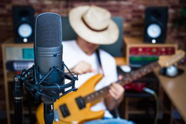 condenser microphone on male musician playing electric guitar in music studio background
