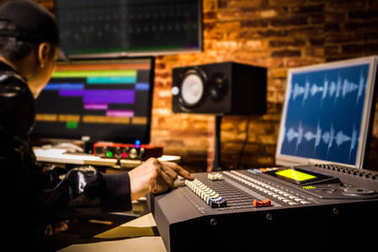 Asian male professional sound engineer working in digital recording, broadcasting, editing studio. focus on mixer fader stock vector