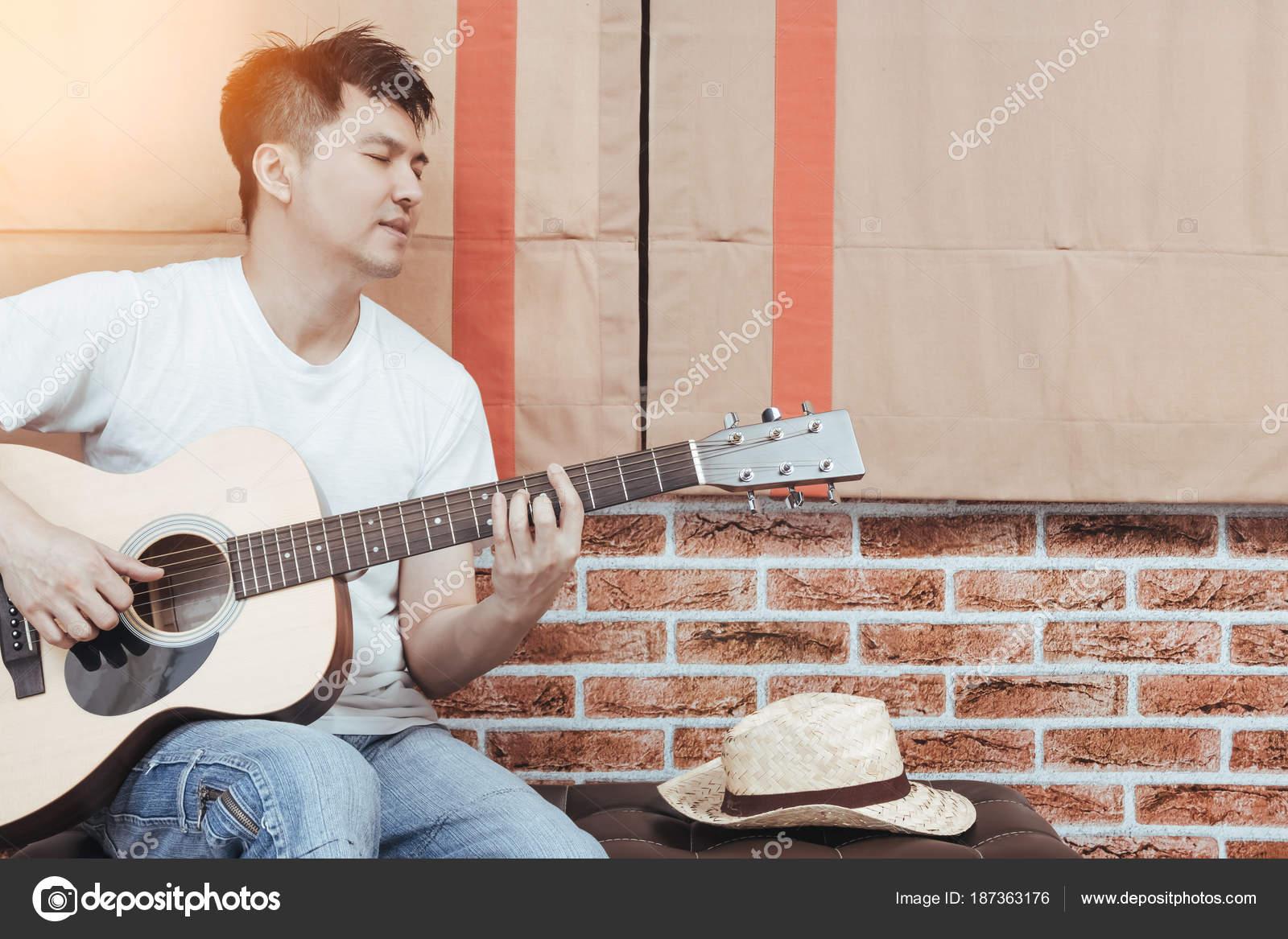Uomo bello asiatico che gioca chitarra acustica sgabello loft design