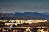 Fotografie Sluncem zalité barevné bloky a hory v Banské Bystrici